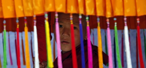 Image: A young monk holds a traditional parasol as he waits for the arrival of Tibet